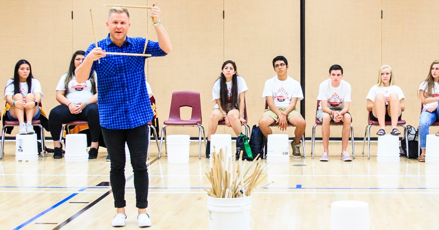 clint pulver holding up drum sticks in front of students for a workshop