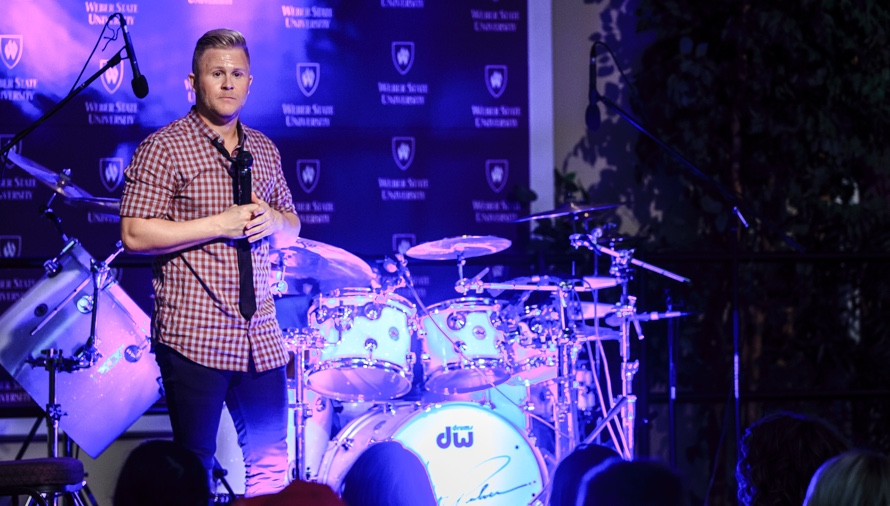 clint pulver speaking at westminster college with drumset
