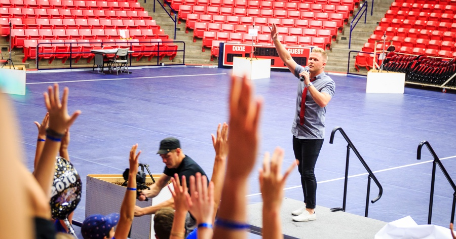 clint speaking to students in an arena while holding his hand up