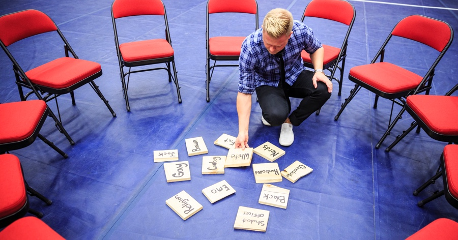 clint pulver bent down holding pieces of wood that has words on it for a workshop course